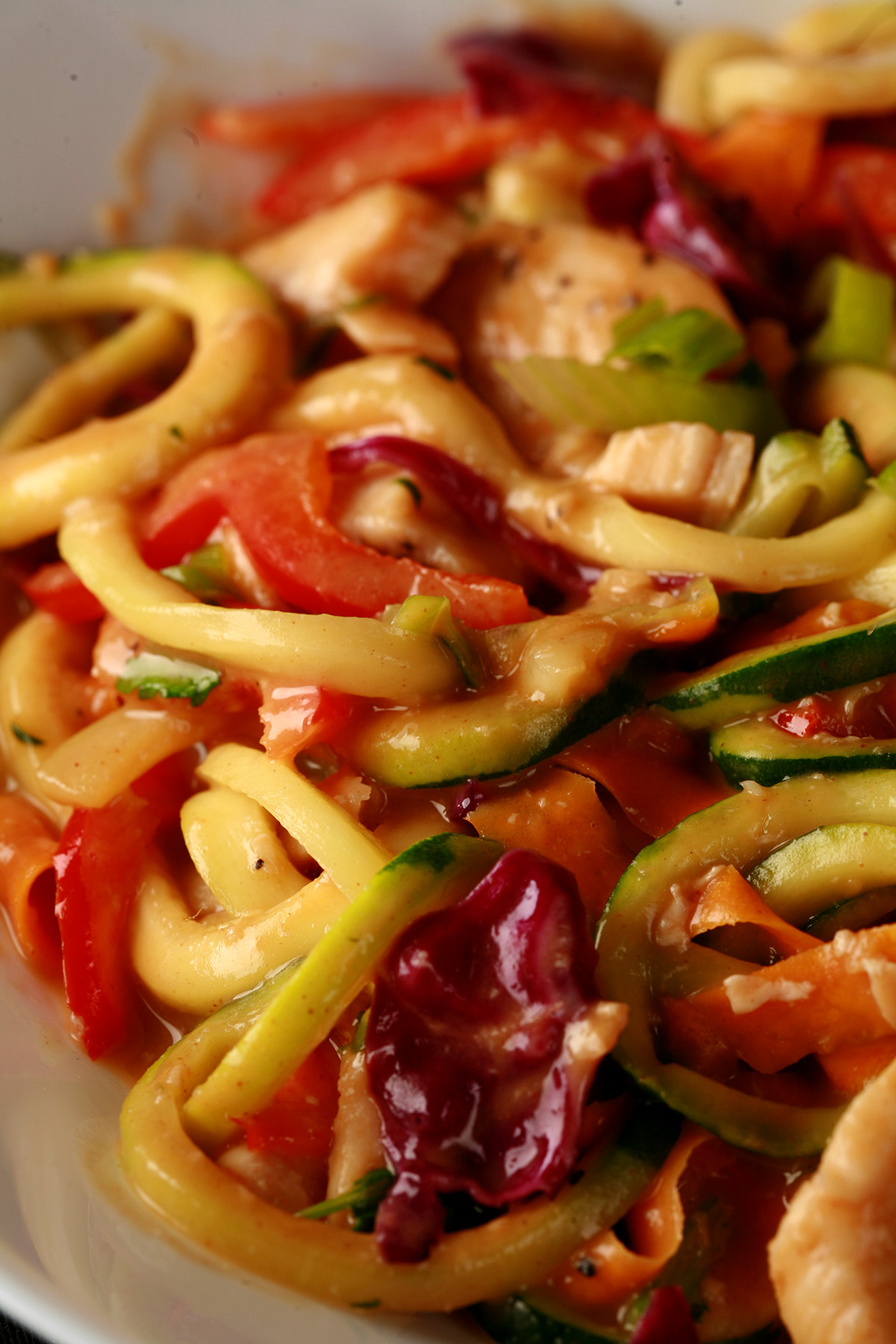 A close up view of a colourful low carb peanut chicken zoodles dish - zucchini noodles, purple cabbage, carrot strups, thinly sliced red pepper, green onions, and cilantro, in a translucent peanut sauce.