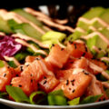 Close up view of a keto spicy salmon poke bowl - chunks of marinated salmon and veggies, drizzled with a light pink dynamite sauce.