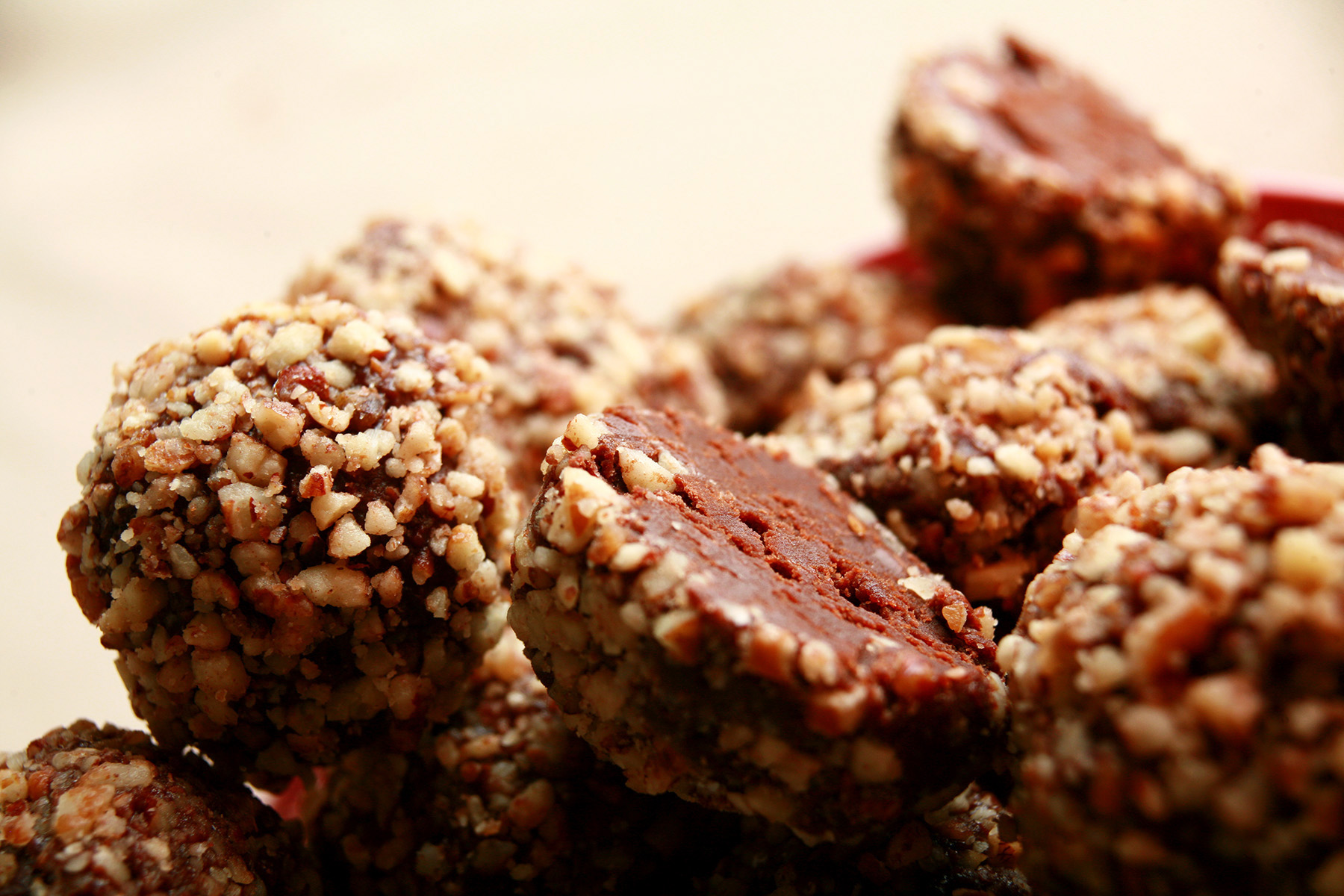 A red plate piled high with low carb bananas foster truffles. They are coated in crushed pecans.