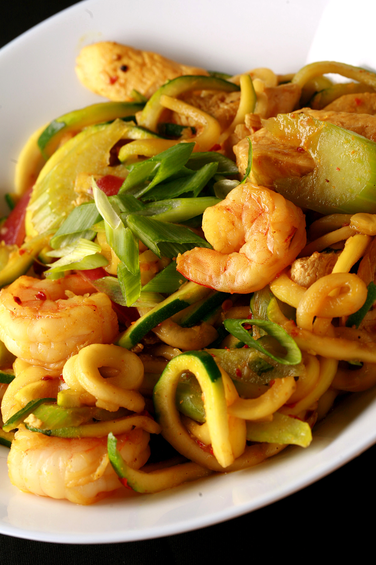 A white bowl with singapore mai fun style zoodles.