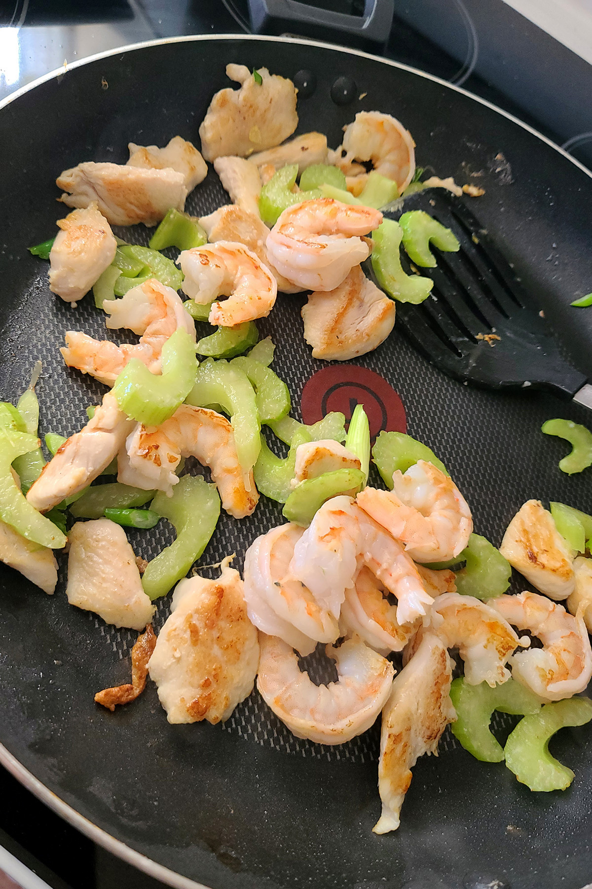 Chicken, shrimp, and celery cooking in a pan.