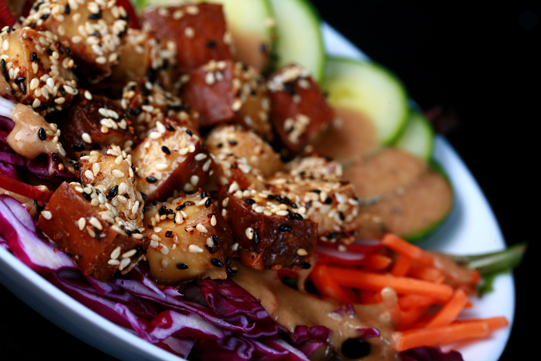 sesame crusted smoked tofu on top of a colourful salad. Cucumbers, beets, carrots, and purple cabbage are visible.